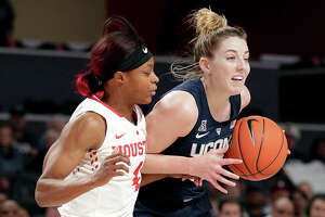 Houston guard Jasmyne Harris, left, defends as Connecticut guard/forward Katie Lou Samuelson (33) drives to the basket during the first half of an NCAA college basketball game Sunday, Jan. 6, 2019, in Houston. (AP Photo/Michael Wyke)