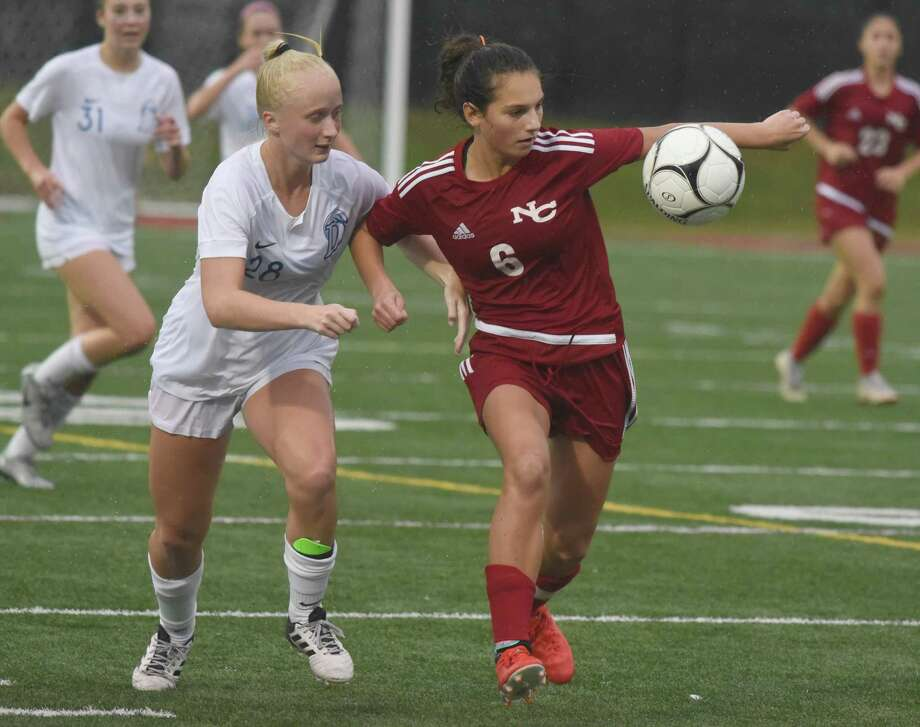 Darien's Eleanor Mellin (28) and New Canaan's Kaleigh Harden (6) battle for the ball in the rain during a girls soccer game at New Canaan's Dunning Field on Wednesday, Oct. 16, 2019. Photo: Dave Stewart / Hearst Connecticut Media / Hearst Connecticut Media