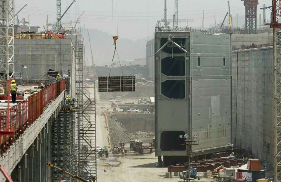 Construction crews work on the the Panama Canal expansion project new set of locks, while the last rolling gate is installed in Cocoli, near Panama City, Tuesday, April 28, 2015. The Panama Canal Authority supervised the installation of the last of 16 giant lock gates that are a key part of the waterway's multibillion-dollar expansion. The construction of the third set of locks will allow the passage of Post-Panamax vessels or container ships much too big to fit through the Panama Canal's old locks. (AP Photo/Arnulfo Franco) Photo: Arnulfo Franco / File Photo By Arnulfo Franco/The Associated Press / AP