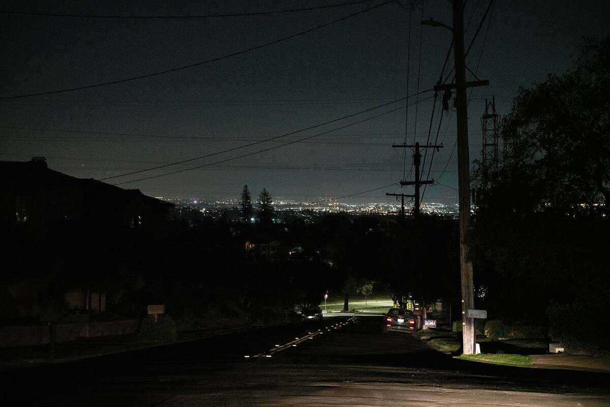 Lights from San Francisco are seen in the distance from Wyngaard Avenue and Estates Drive, when the Oakland neighborhood's power was shut off by PG&E earlier this week.