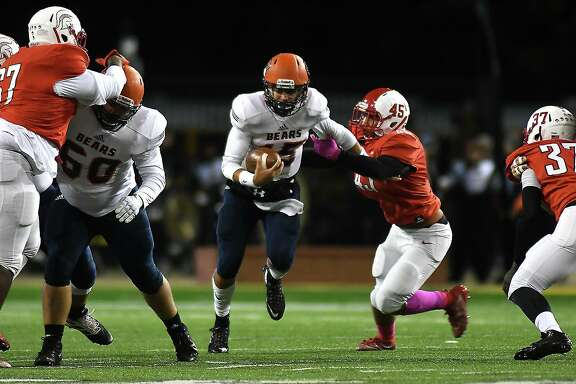 Bridgeland sophomore quarterback Conner Weigman, center, tries to break the grasp of Cy Lakes defender Givon Ortega Jones (45) in the first quarter of their District 14-6A matchup at Cy-Fair FCU Stadium in Cypress on Oct. 31, 2019.
