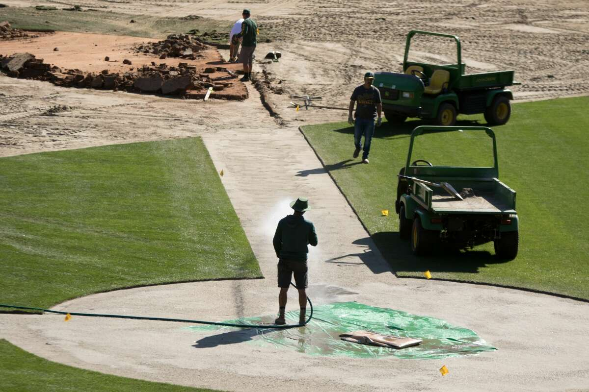 Groundskeepers start the conversion the field of the Oakland Coliseum from a baseball to a football field.
