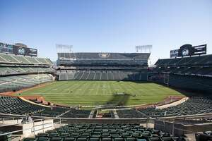 Groundskeepers paint the white football lines as they convert the field of the Oakland Coliseum from a baseball to a football field.