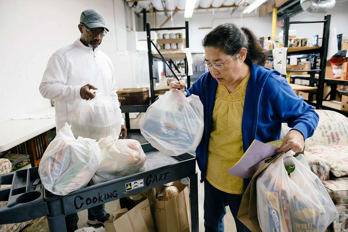 Volunteers David Hines and Pam Sera bag up groceries for the needy in the food bank warehouse of The Well Community Outreach Center in Livermore, California, on Friday, November 1st, 2019.