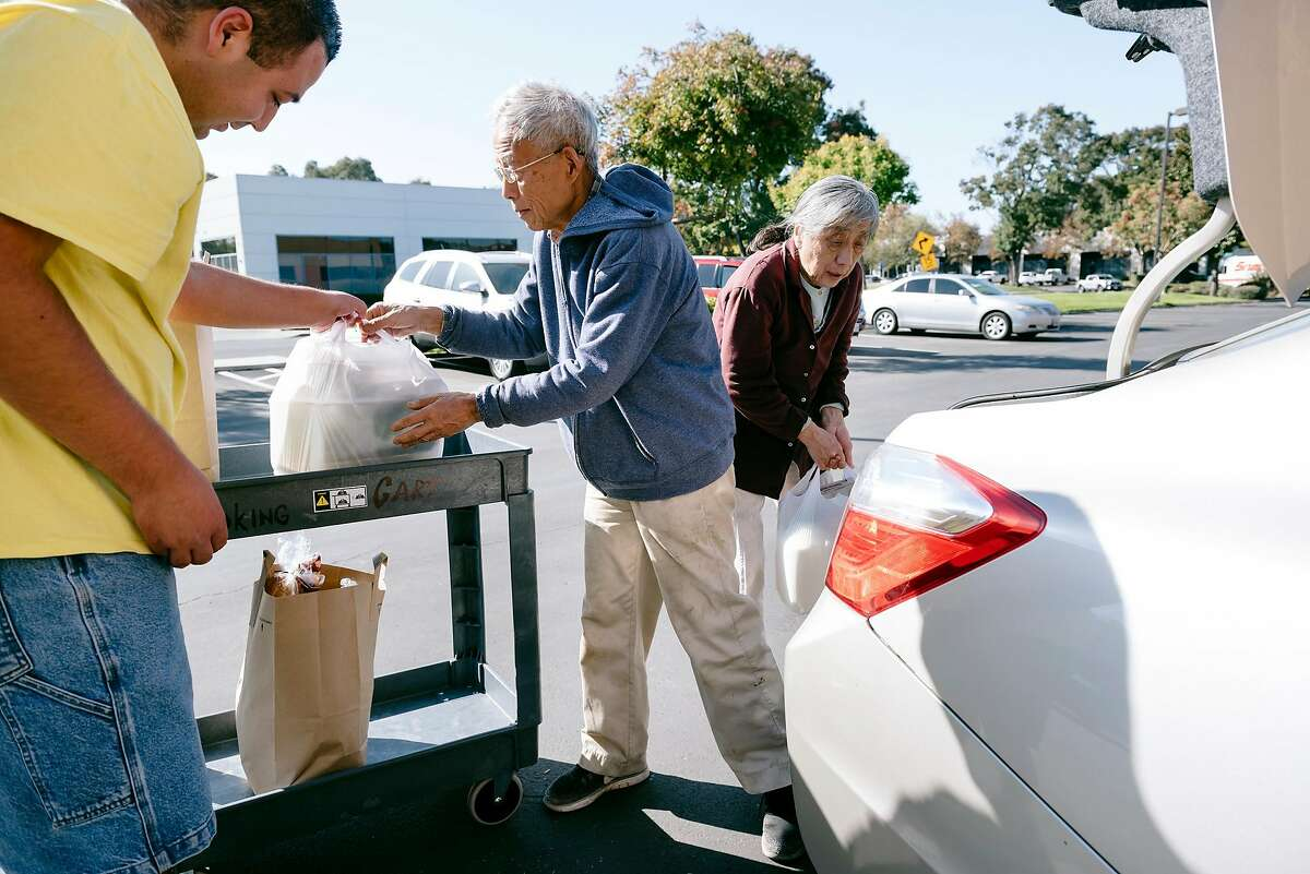 Volunteer Angel Negrete, left, helps load a grocery donation into the car of food bank clients Shenge Yu, and Fengle Hu at The Well Community Outreach Center in Livermore, California, on Friday, November 1st, 2019.