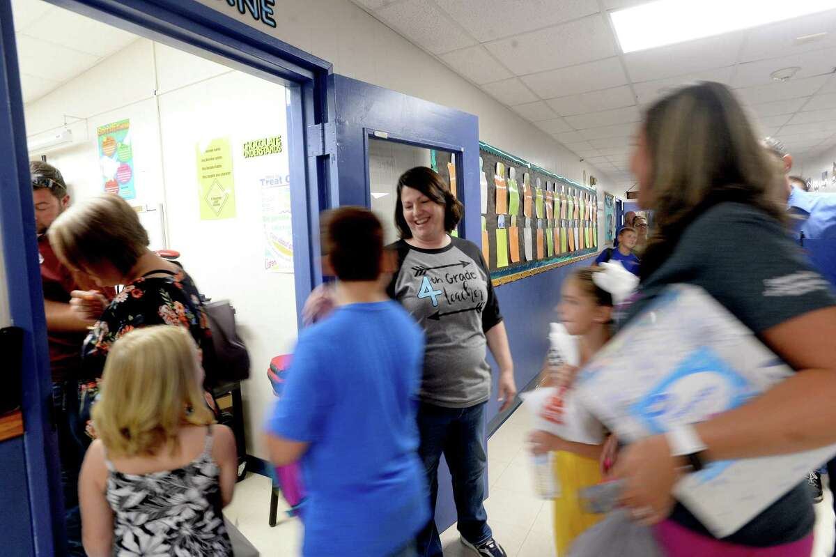 Fourth grade teacher Duska Bourne greets students and parents to her classroom during a