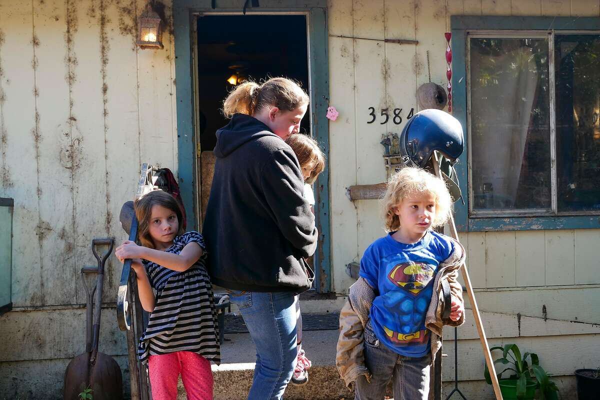 Jessica Howell holds her 4 year old daughter Hazel Black as she stands with her other children, 7 year old Zoe Barney and twin brother Matthew Barney, Friday November 1, 2019, outside their home in Clearlake, CA.