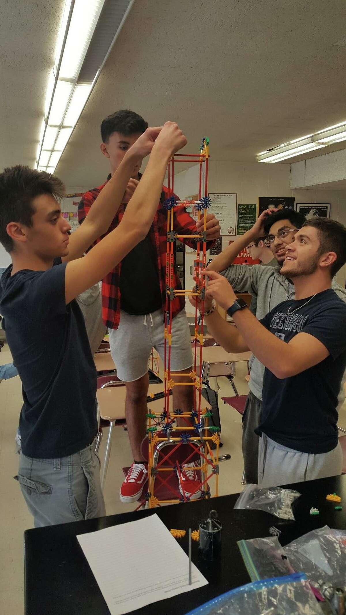 David Teti, John McLaughlin, Muhammad Saleem and Justin Mattiello construct a K'Nex tower they designed using the engineering design process.