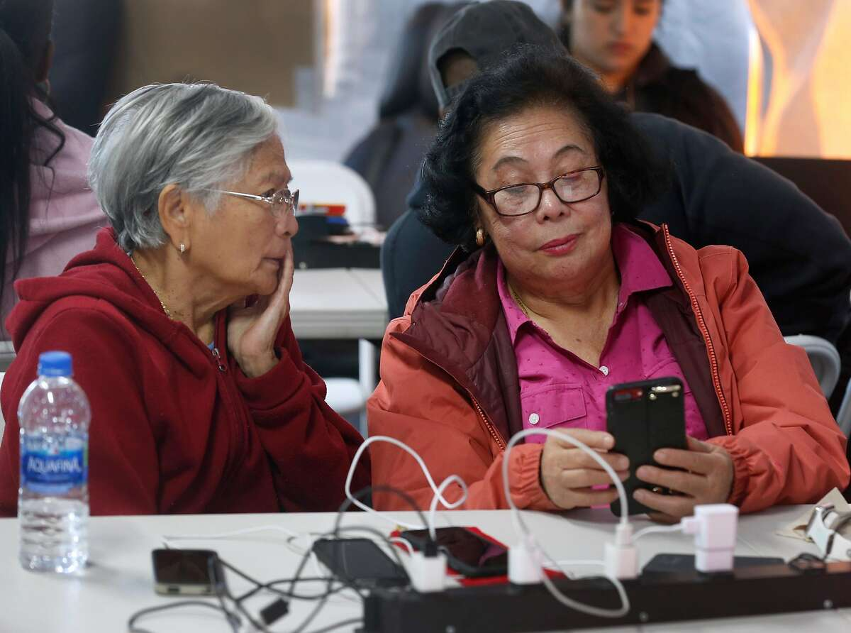 Florida Garcia (left) and Doris Beltran wait for the cell phones to recharge at the PG&E community resource center at the Solano County Fairgrounds as the public safety power shutoff issued by the utility company continues for a third consecutive day in Vallejo, Calif. on Tuesday, Oct. 29, 2019.
