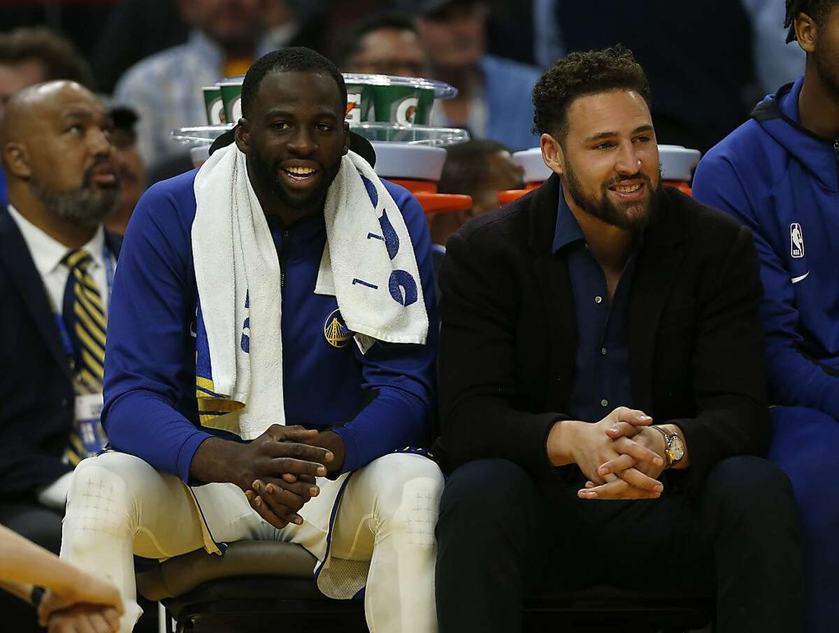 In this Wednesday, Oct. 30, 2019 photo, Golden State Warriors' Draymond Green, left, and Klay Thompson (11) sit on the bench in the fourth quarter of an NBA basketball game against the Phoenix Suns in San Francisco, Calif.