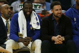 In this Wednesday, Oct. 30, 2019 photo, Golden State Warriors' Draymond Green, left, and Klay Thompson (11) sit on the bench in the fourth quarter of an NBA basketball game against the Phoenix Suns in San Francisco, Calif. In an eyeblink, the Warriors have tumbled from the mountaintop to possible lottery pick. One Splash brother was already out and now Steph Curry joins him with a broken hand. It is left to Draymond Green to anchor a decimated roster for a bid to just to make the playoffs. (Nhat V. Meyer/San Jose Mercury News via AP)