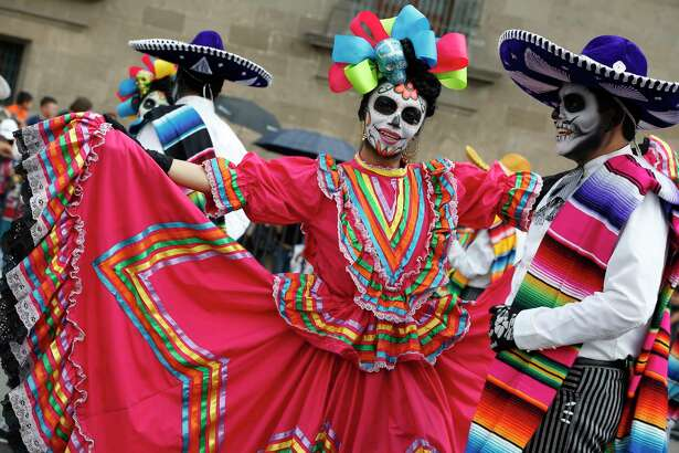 Performers in costume attend a Day of the Dead parade in Mexico City, Sunday, Oct. 27, 2019.(AP Photo/Ginnette Riquelme)