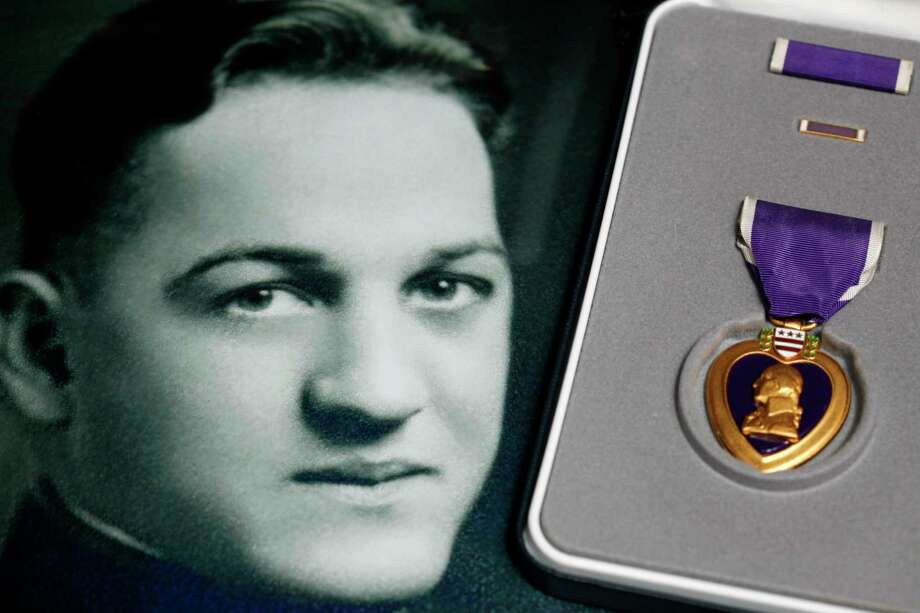 FILE - This May 6, 2010 file photo, shows a portrait of Coast Guard Lt. Thomas J.E. Crotty next to a Purple Heart medal, one of several medals presented posthumously in Buffalo, N.Y. The remains of Crotty, a Coast Guardsman who died as a prisoner of war during World War II, has returned home to Buffalo for a funeral his relatives have been awaiting for decades. His remains were identified in September, 77 years after his death from diphtheria in a Japanese POW camp. (AP Photo/David Duprey, File) Photo: David Duprey / Copyright 2019 The Associated Press. All rights reserved.