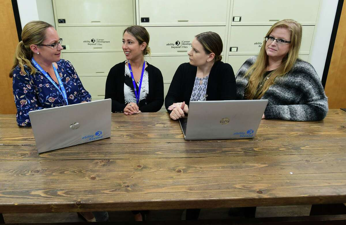 Employees including Kate Travis, Jennifer Pratt, Kaitlyn Appley and Amber Sullivan discuss their clients at The Bethel-based disabilities services giant, Ability Beyond facility in Norwalk. October is national disabilities awareness month.