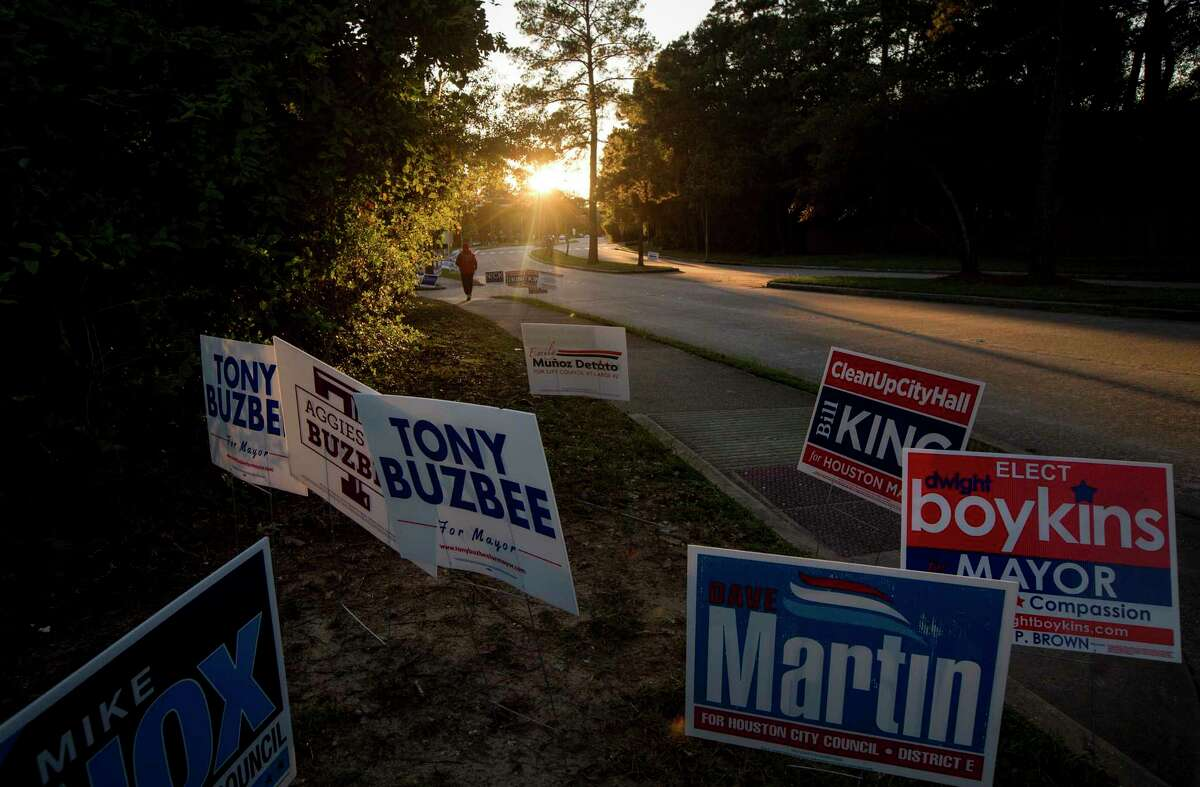 A jogger passes campaign signs at Kingwood Park Community Center on Thursday, Oct. 31, 2019, in Houston.
