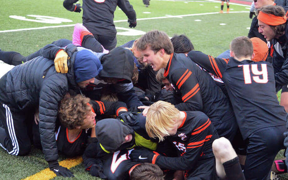 Edwardsville players pile on top of Brennan Weller after Weller scored the game-winning goal with no time left on the clock in the second half in Friday's game against Moline in the finals of the Class 3A Normal West Sectional at Bloomington High School.