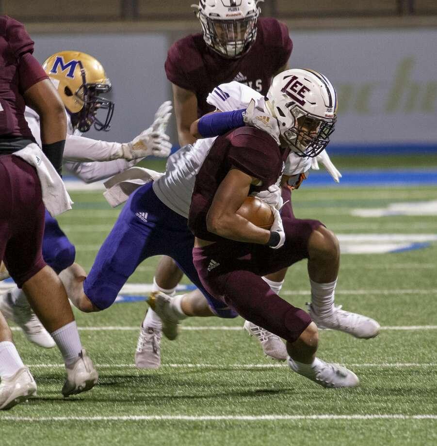Lee's Christian Romero runs the ball as Midland High's Martin Flores tackles him Friday, Nov. 1, 2019 at Grande Communications Field. Photo: Jacy Lewis/Reporter-Telegram