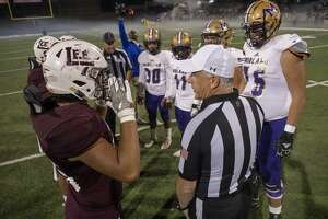 Lee and Midland High meet at the 50 yard line to flip a coin Friday, Nov. 1, 2019 at Grande Communications Field.