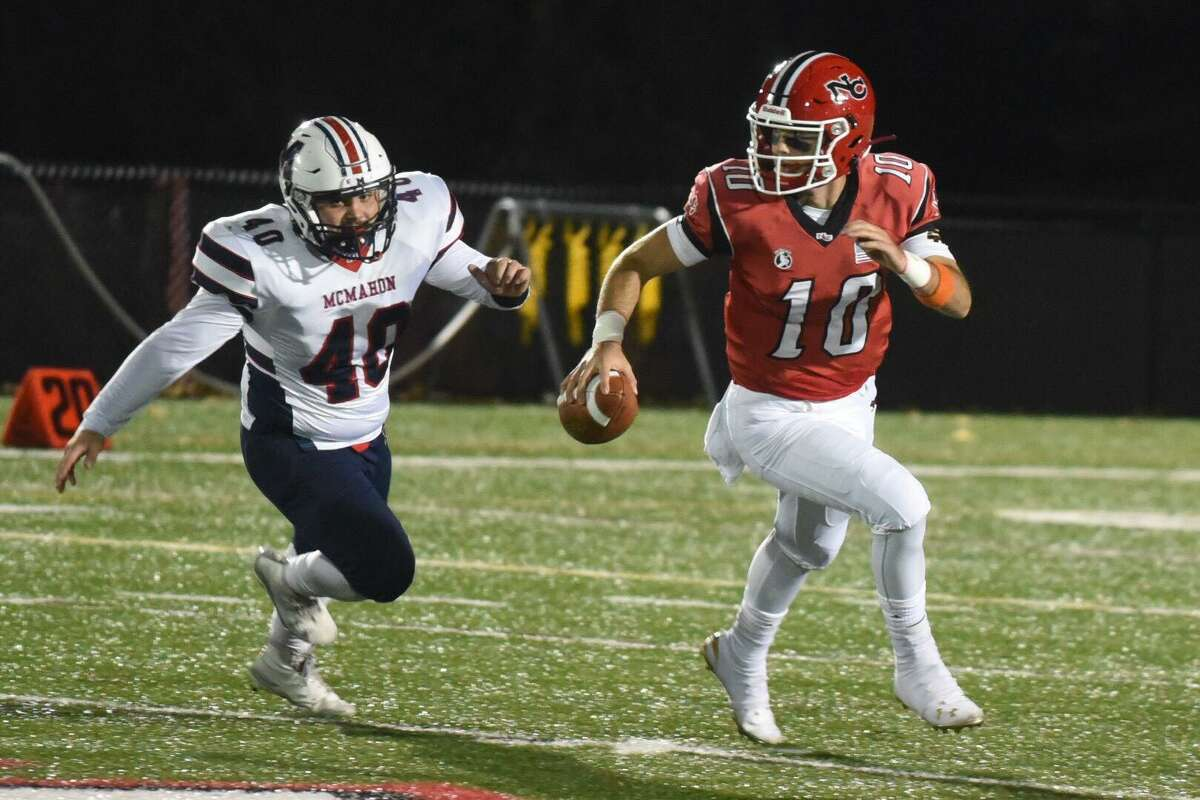 New Canaan QB Drew Pyne (10) scrambles away from Brien McMahon's Jeffrey Cocchia (40) during a football game at Dunning Field in New Canaan on Friday, Nov. 1, 2019.