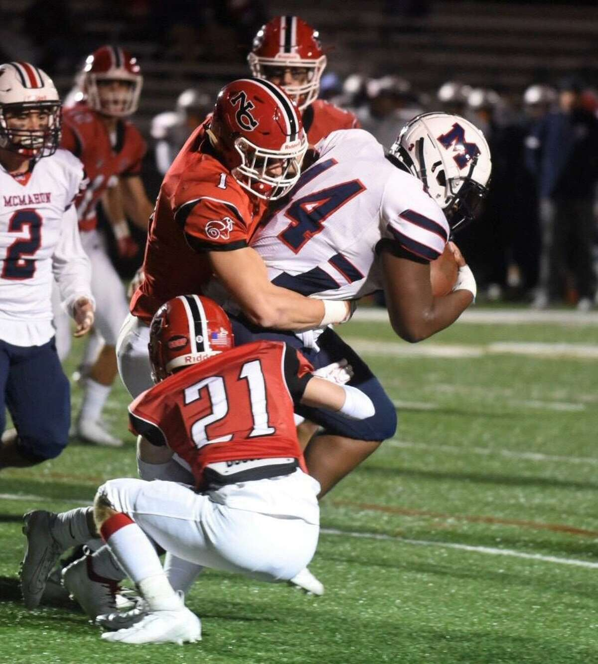 Brien McMahon's Jermayne Daniel (44) is wrapped up by New Canaan's Chris Carratu (1) and Dean Ciancio (21) during a football game at Dunning Field in New Canaan on Friday, Nov. 1, 2019.