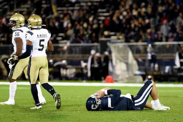 Connecticut quarterback Jack Zergiotis (11) lies on his back after fumbling the ball at the 2-yard line during the first half of the team's NCAA college football game against Navy, Friday, Nov. 1, 2019, in East Hartford, Conn. Navy recovered the fumble. (AP Photo/Stephen Dunn)