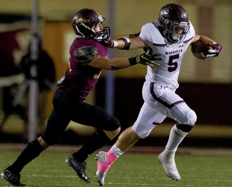 Magnolia running back Mitch Hall (5) stiff-arms Magnolia West linebacker Petton Dyess (36) during the third quarter of a District 8-5A high school football game at Magnolia West High School, Friday, Nov. 1, 2019, in Magnolia. Photo: Jason Fochtman, Houston Chronicle / Staff Photographer / Houston Chronicle