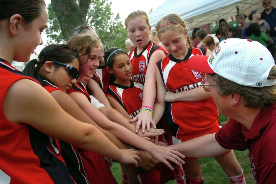 Coach Dave McCartney (right) gathers with members of the age 9-10 Fairfield Little League Softball team Monday, Aug. 9th, 2010, in Fairfield, Conn., where the team was honored by the town for being New England Champions. Photo: Ned Gerard / Connecticut Post