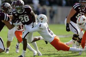COLLEGE STATION, TEXAS - NOVEMBER 02: Isaiah Spiller #28 of the Texas A&M Aggies rushes with the ball as SaVion Harris #6 of the UTSA Roadrunners attempt to make the tackle during the first half at Kyle Field on November 02, 2019 in College Station, Texas.