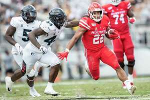 Houston running back Kyle Porter (22) runs by Central Florida linebacker Nate Evans (44)  during the first half of an NCAA college football game in Orlando, Fla., Saturday, Nov. 2, 2019. (Photo/Willie J. Allen Jr.)