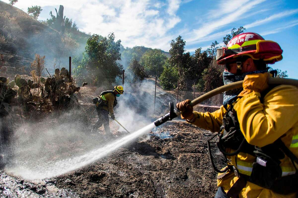 Firefighters from Santa Fe Springs battle to control hotspots of the Maria Fire, in Santa Paula, Ventura County, California on November 02, 2019. - The Maria Fire erupted October 31 in Ventura County, 65 miles (105 kilometers) northwest of Los Angeles, and burned out of control through the night, driven by high winds and threatening 2,300 structures. (Photo by Apu Gomes / AFP) (Photo by APU GOMES/AFP via Getty Images)