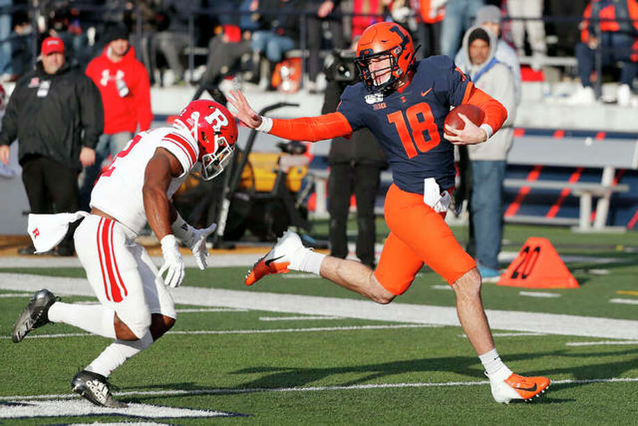 Illinois quarterback Brandon Peters stiff-arms Rutgers defensive back Christian Izien on his way to a 54-yard run during Saturday's game in Champaign. The Illini won 38-10. Photo: AP Photo