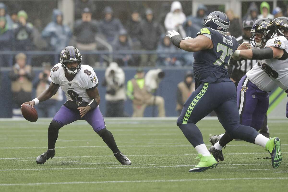 Seattle Seahawks defensive tackle Al Woods, right, pressures Baltimore Ravens quarterback Lamar Jackson, left, during the first half of an NFL football game, Sunday, Oct. 20, 2019, in Seattle. (AP Photo/Elaine Thompson)