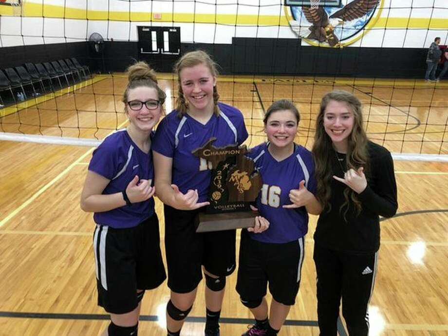 Calvary Baptist seniors (from left) Faith Howell, Bailee Hunger, Kaitlin Schmidt and Sara Lawrence celebrate with the trophy after the team won its sixth straight Michigan Association of Christian Schools Division 1 championship.