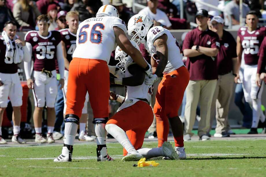 UTSA quarterback Lowell Narcisse, center, gets helped to his feet after taking a hard hit in the third quarter against A&M. Photo: Sam Craft /Associated Press / Copyright 2019 The Associated Press. All rights reserved.