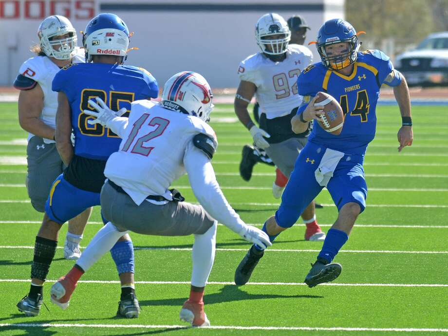 Wayland Baptist quarterback Mitchell Parsley scrambles up the field for yardage while receiver Brayln Kirby tries to shield Oklahoma Panhandle State's Malik Brown during their Sooner Athletic Conference football game on Saturday in Greg Sherwood Memorial Bulldog Stadium. Photo: Nathan Giese/Planview Herald