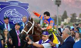 Jockey Irad Ortiz Jr. celebrates in the winner's circle after riding Vino Rosso to victory in the Breeders Cup Classic race at the 2019 Breeders Cup at the Santa Anita Racetrack in Arcadia, California on November 2, 2019. - Joel Rosario riding McKinzie came in 2nd (Photo by Frederic J. BROWN / AFP) (Photo by FREDERIC J. BROWN/AFP via Getty Images)