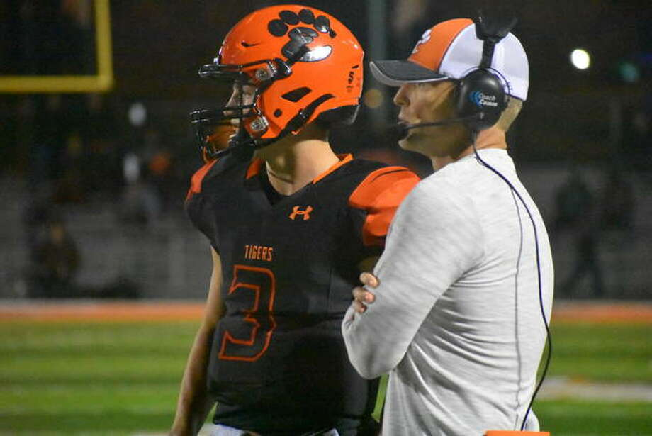 EHS quarterback Ryan Hampton, left talks to assistant coach Jason Osborn during the second quarter against St. Charles East. Photo: Matt Kamp|The Intelligencer