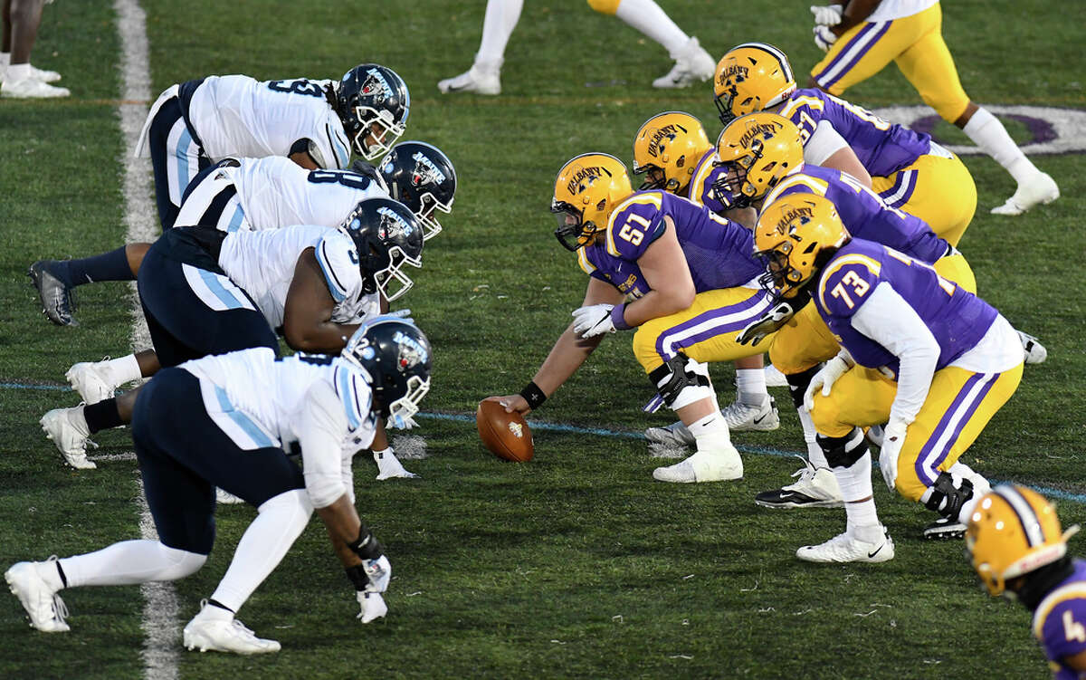 Maine defensive players ,left, match up University at Albany offensive players during an NCAA football game Saturday, Nov. 2, 2019, in Albany, N.Y.