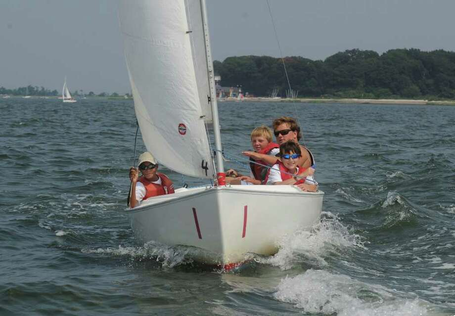 From left, Jaden Williams, 10, Ben Orszulak, 11, teacher Brian Schapperle, and Brian Kelly, 12, sailing with the Greenwich Young Mariners program at Greenwich Harbor, on Monday, Aug. 9, 2010. 8/10/10 GT photo = Taking a new tack. At the Point: Young Mariners Foundation helps kids sail through course offering. by Lisa Chamoff Photo: Helen Neafsey, Greenwich Time / Greenwich Time