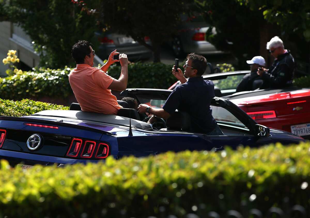 Tourists take pictures while driving down Lombard Street n San Francisco.