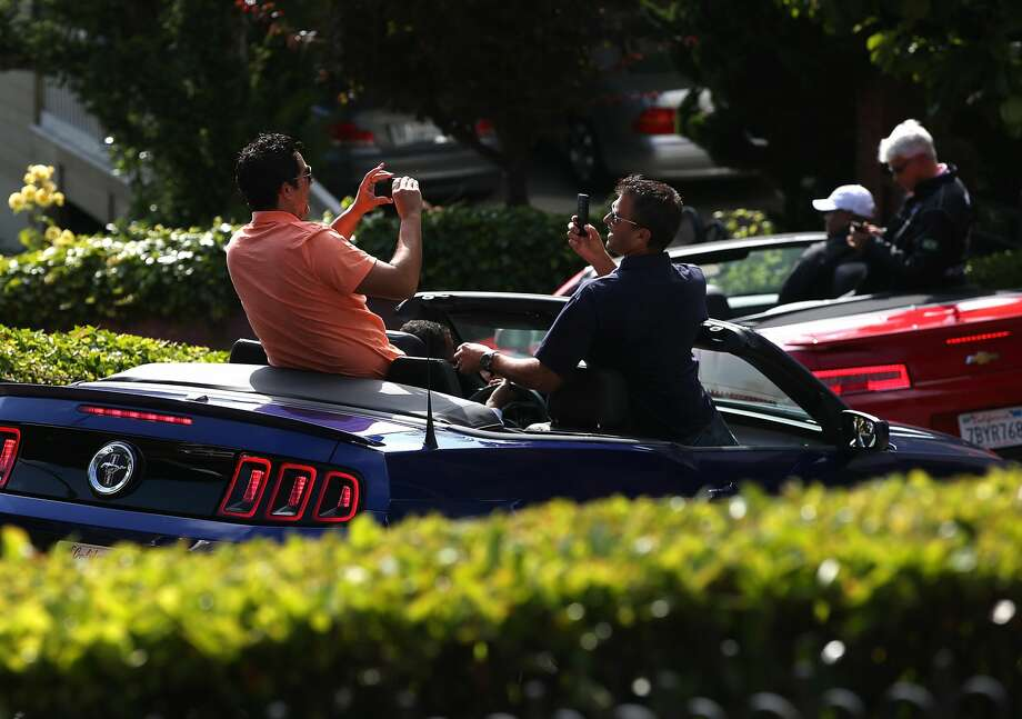Tourists take pictures while driving down Lombard Street n San Francisco. Photo: Justin Sullivan/Getty Images