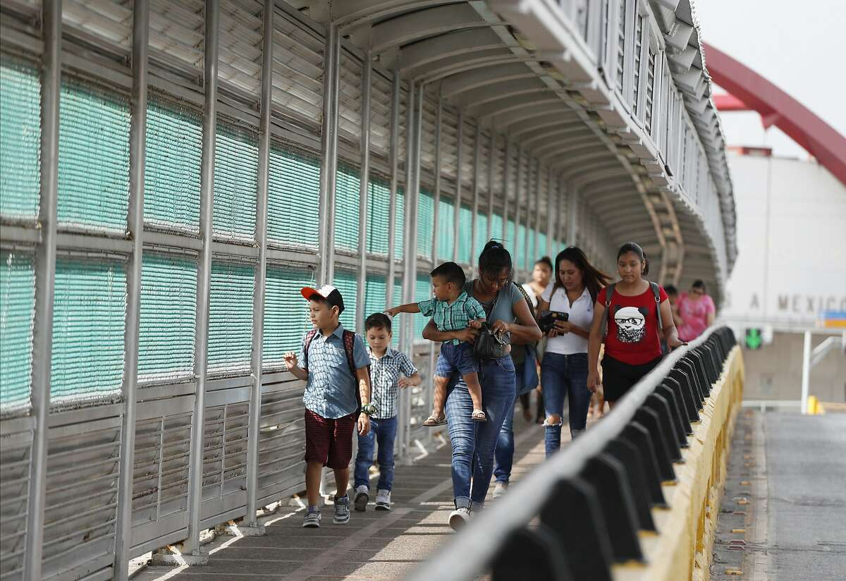 Residents with visas walk across the Puerta Mexico international bridge in Matamoros to enter the U.S., in June 2019. On Thursday, a federal appeals court ruled that President Trump has the power to to bar immigrants from the U.S. who cannot afford private health insurance, a ban that would affect as many as 375,000 people a year if it takes effect.