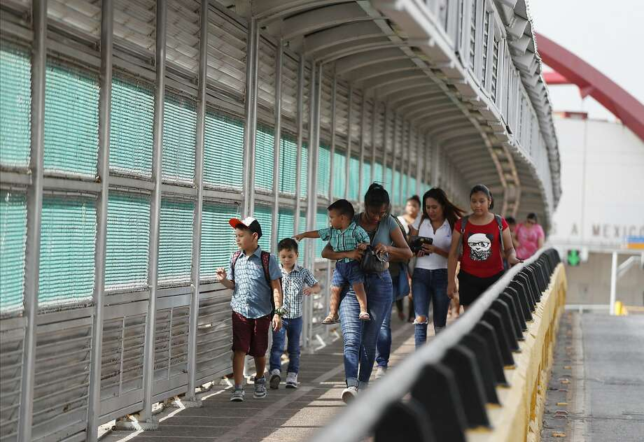 FILE - In this June 28, 2019 file photo, local residents with visas walk across the Puerta Mexico international bridge to enter the U.S., in Matamoros, Tamaulipas state, Mexico. A federal judge in Portland, Ore., on Saturday, Nov. 2, 2019, put on hold a Trump administration rule requiring immigrants prove they will have health insurance or can pay for medical care before they can get visas. U.S. District Judge Michael Simon granted a preliminary injunction that prevents the rule from going into effect Sunday. (AP Photo/Rebecca Blackwell, File) Photo: Rebecca Blackwell, Associated Press
