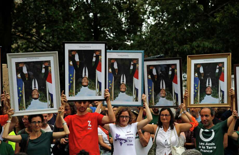 FILE - In this Aug.25, 2019 file photo, demonstrators hold up upside down portraits of French President Emmanuel Macron during a protest in Bayonne, France. One by one, environmental activists around France have been taking portraits of President Emmanuel Macron down from scattered town halls this year. The portrait-removers, have been facing trials around the country, with some fined, others released. An appeals court in Lyon is reconsidering the first conviction handed down over portrait removal Tuesday. (AP Photo/Emilio Morenatti, File) Photo: Emilio Morenatti / Associated Press / Copyright 2019 The Associated Press. All rights reserved