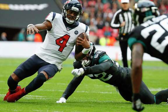 Houston Texans quarterback Deshaun Watson (4) slides for a first down, chased down by Jacksonville Jaguars linebacker Najee Goode (52) during the second quarter of an NFL football game at Wembley Stadium on Sunday, Nov. 3, 2019, in London.