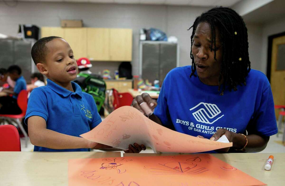 """Keyon Brown, 5, presents Tamarya Guess, 44, a drawing he created at the Eastside Branch of the Boys & Girls Clubs of San Antonio in San Antonio, Texas, on Oct. 21, 2019. Guess has been working with the Boys & Girls Club of San Antonio as a lead youth development professional for eight months and says that her """"life mission is to be an advocate and a voice for those who don't have a voice."""""""