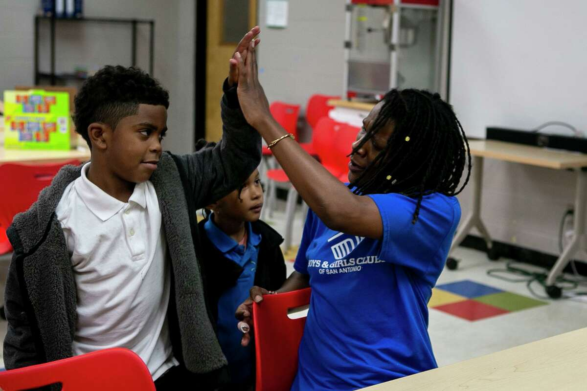 Tamarya Guess, 44, high fives Noah Stacy Beamer, 7, at the Eastside Branch of the Boys & Girls Clubs of San Antonio in San Antonio, Texas, on Oct. 21, 2019.