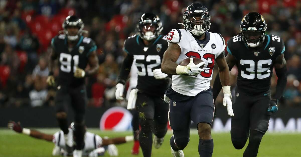 Houston Texans running back Carlos Hyde (23) runs past Jacksonville Jaguars strong safety Ronnie Harrison (36) during the fourth quarter of an NFL football game at Wembley Stadium on Sunday, Nov. 3, 2019, in London.