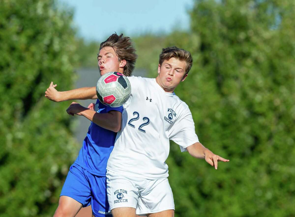 Jake Lash (right) vies for a header with a Darien player.