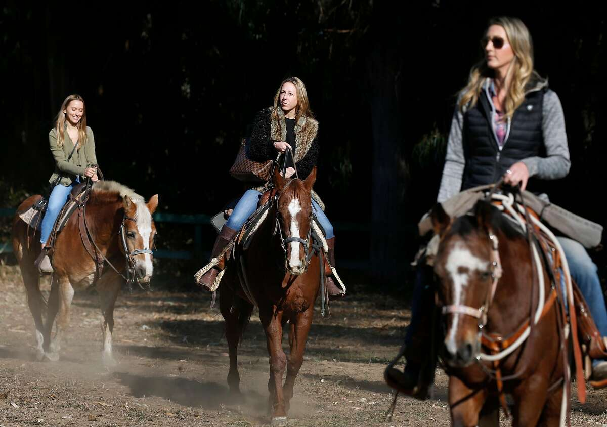 Karolina Dadej (left) and Koren Cohen (center) are led around the Bercut Equitation Field ring by Ashley Molnar (right) before a 30-minute trail ride through Golden Gate Park in San Francisco, Calif. on Saturday, Nov. 2, 2019. Chaparral Ranch is providing riding lessons and trail rides at the park for the first time in nearly 20 years.